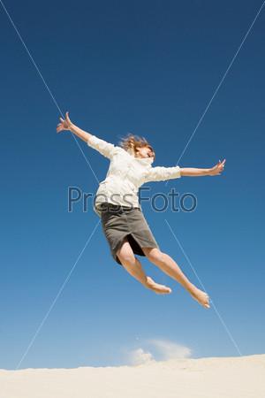 Задорная девушка подпрыгивает на песчаном пляже на фоне неба