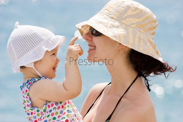Малышка в панамке трогает маму за нос и смеется