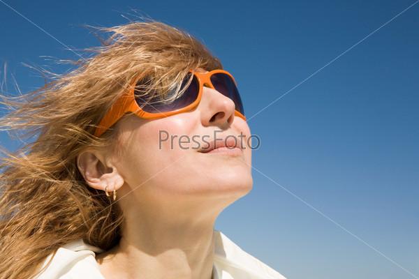Красивая девушка в солнцезащитных очках стоит на фоне неба, ее волосы развеваются на ветру