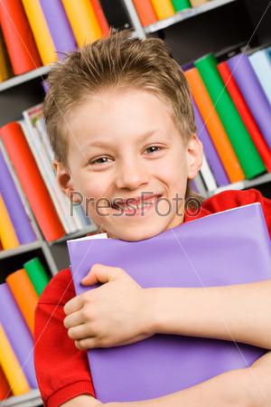 Улыбающийся ученик стоит на фоне книжной полки со стопкой папок в руках