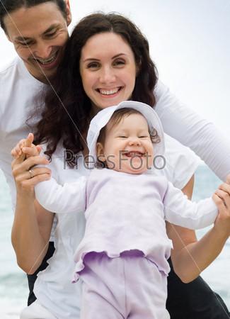 Счастливая семья держится за руки и смотрит в камеру