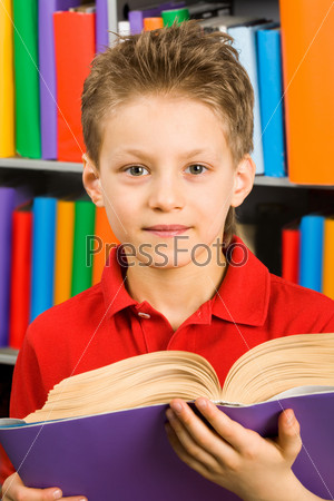 Довольный мальчик смотрит в камеру с раскрытой книгой на фоне полок в библиотеке