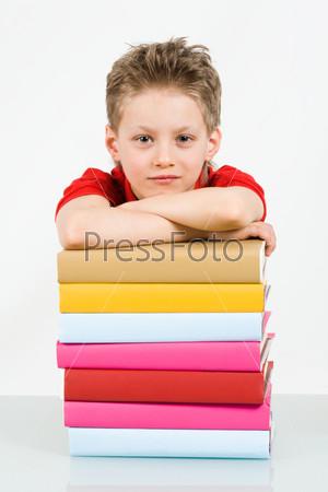 Привлекательный мальчик самоуверенно смотрит в камеру облокотясь на стопку ярких книг