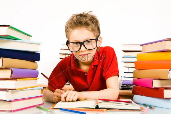 Продвинутый ученик в очках сидит за партой в окружении кипы учебников