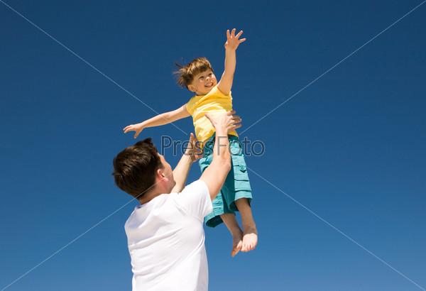 Папа подкидывает вверх счастливого малыша на фоне синего неба