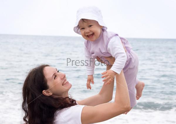 Счастливая мама поднимает вверх смеющуюся дочь в чепчике на фоне моря