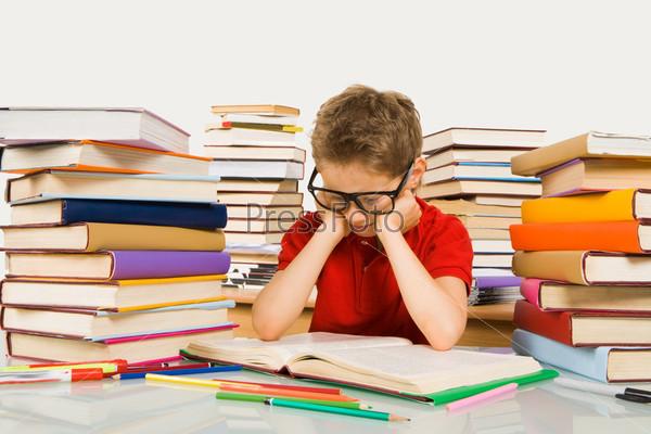 Усердный ученик в очках сидит за столом в окружении высоких стопок книг