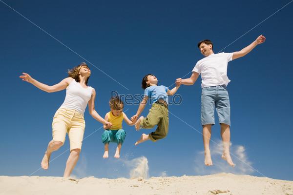 Фотография на тему Счастливая семья прыгает на песке держжась за руки