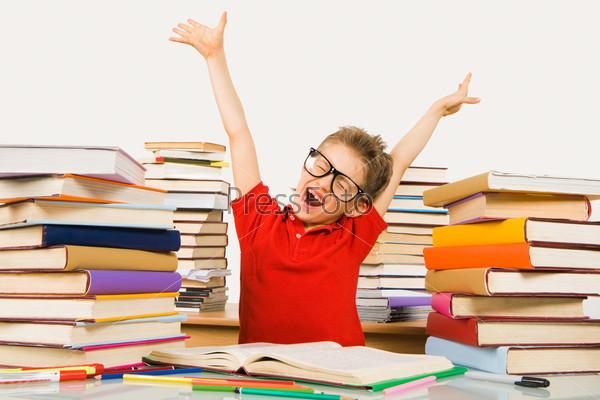 Счастливый школьник выполнил уроки и поднял руки вверх крича от радости