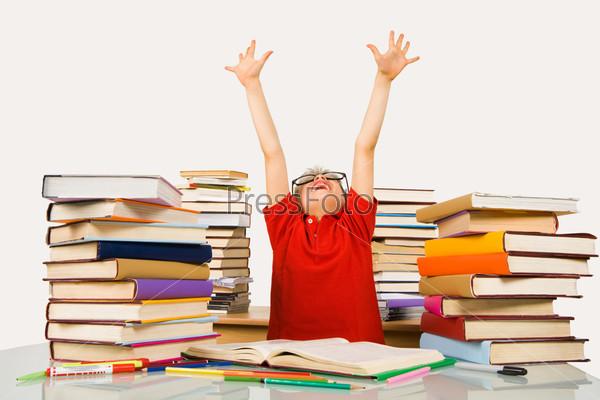 Школьник выполнив уроки поднял в восторге руки вверх сидя в окружении учебников
