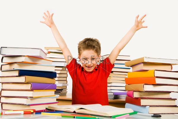 Довольный ученик поднял руки вверх в окружении учебников