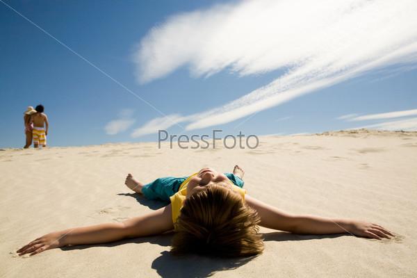Отдыхающий мальчик лежит на песке раскинув руки и глядя в небо на фоне своих родителей стоящих на горизонте