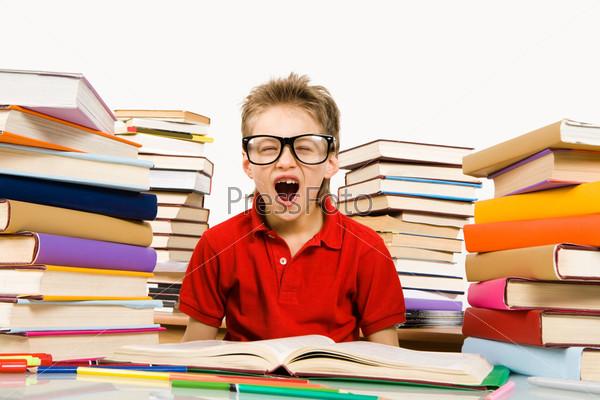 Фотография на тему Школьник выполняет задание в окружении стопок с учебниками и зевает