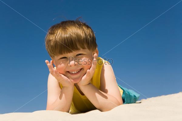 Мальчик смеясь смотрит в камеру лежа на песке