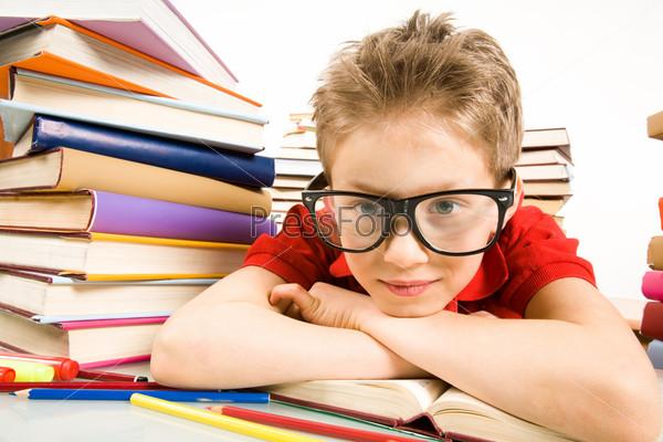 Крупный план мальчика в больших очках, который лег на парту в окружении учебников