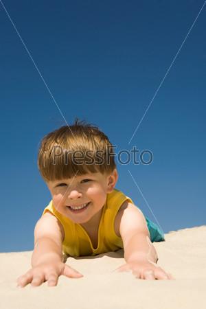 Фотография на тему Счастливый мальчик растянувшись на песке смотрит в камеру и улыбается