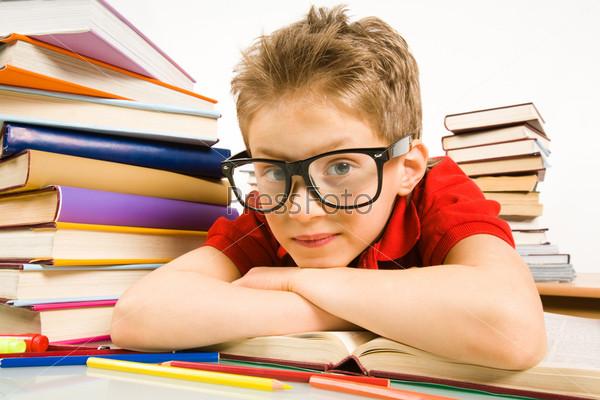 Школьник в больших очках смотрит в камеру лежа на учебнике в окружении больших стопок книг