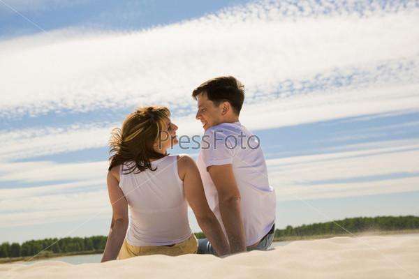 Красивая пара сидит спиной к камере на песке и разговаривает
