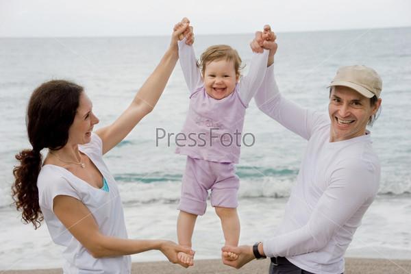 Маленькую девочку держат за руки и за ноги папа с мамой на фоне моря