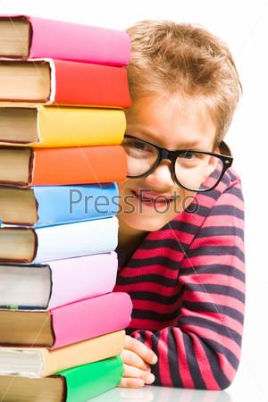 Ученик хитро выглядывает из-за стопки с разноцветными книгами