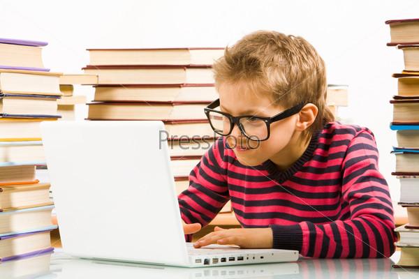Трудолюбивый ученик увлеченно работает на компьютере в окружении стопок книг