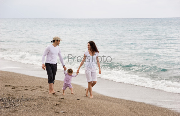 Счастливая семья прогуливается по побережью, держа за руки маленькую дочь