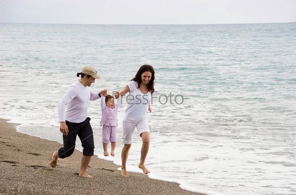 Мама с папой бегут по побережью держа за руки свою маленькую дочь