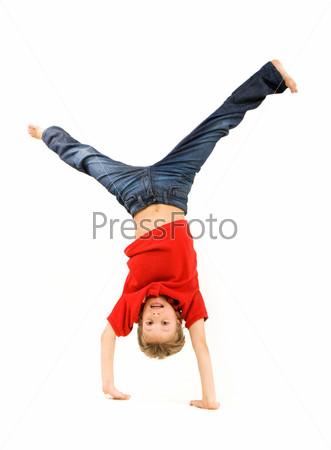 Мальчик в красной футболке стоит на руках и смеется на белом фоне