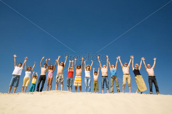 Большая компания стоит в одну линию на песке подняв руки вверх на фоне неба
