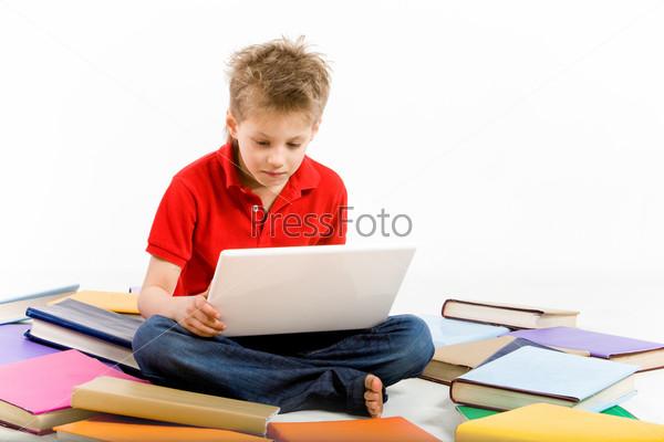 Босоногий мальчик сидит на полу за ноутбуком в окружении разбросанных учебников