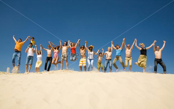 Большая группа друзей подпрыгивает на песке держась за руки