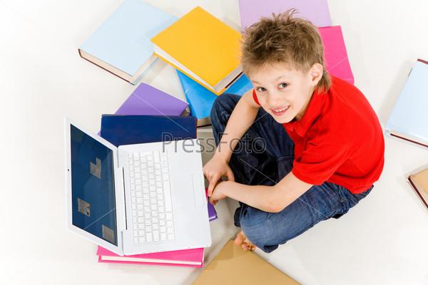 Вид сверху мальчика сидящего на полу за ноутбуком в окружении разбросанных учебников