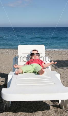 Маленькая девочка лежит в шезлонге на морском побережье в больших темных очках