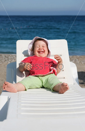 Маленькая девочка лежит в шезлонге на фоне моря и хохочет