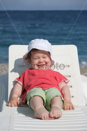Довольная девочка сидит вытянув ноги в шезлонге на фоне моря и улыбается