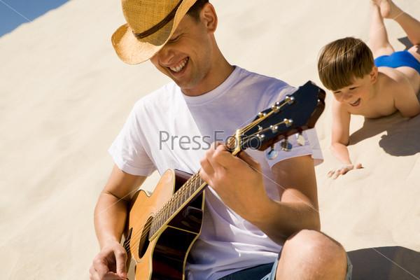 Мужчина играет на гитаре сидя на песке, сзади подкрадывается его сын