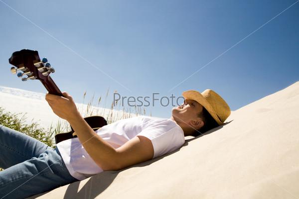 Мужчина с гитарой и в шляпе лежит на песке, вид сбоку