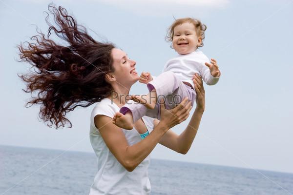 Счастливая мама несет на руках свою радостную дочь