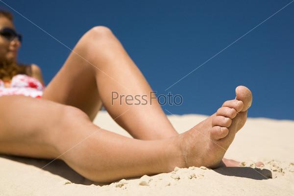 Крупный план стройных ног, лежащих на песке