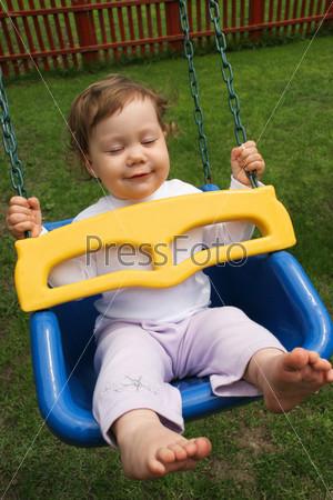 Фотография на тему Маленькая девочка сидит на качелях и жмурится от удовольствия