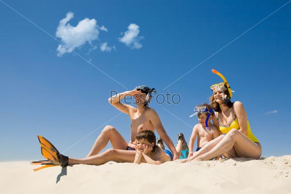 Счастливая семья в пляжной одежде сидит на песке на фоне голубого неба
