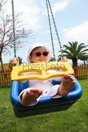 Забавная девочка сидит на качели на детской площадке
