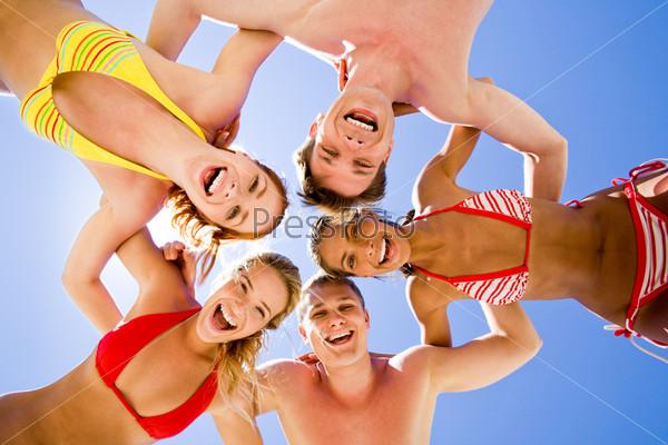 Компания молодых людей в купальниках стоит обнявшись и смотрит вниз в центр камеры