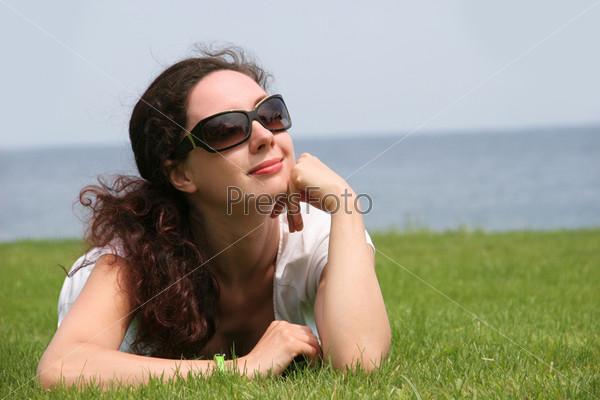 Красивая брюнетка лежит на траве на фоне водоема