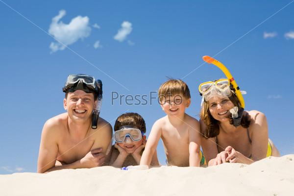 Семья из четрех человек лежит на песке в масках для подводного плавания