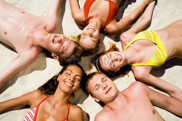Веселая компания лежит на песчаном пляже, образуя круг головами, вид сверху