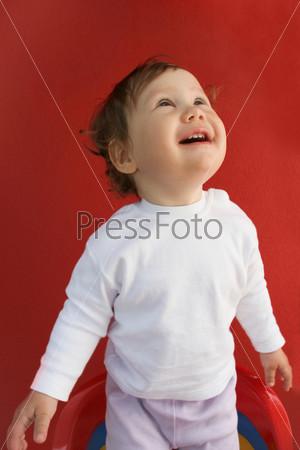 Маленькая девочка стоит на стульчике и удивленно смотрит вверх