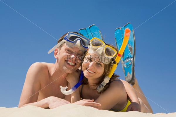 Счастливая пара лежит на песке в костюмах для подводного плавания