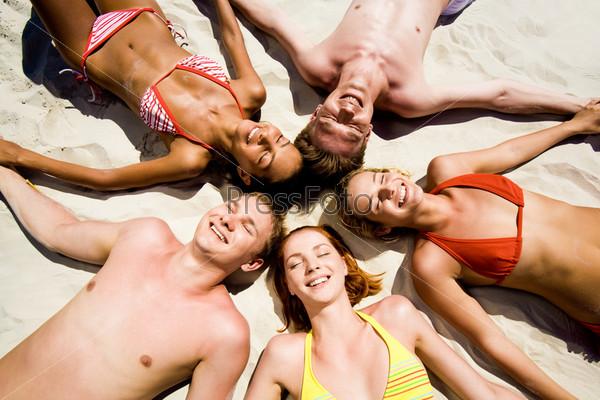 Компания девушек и парней лежат на пляже прижавшись головами и закрыв глаза