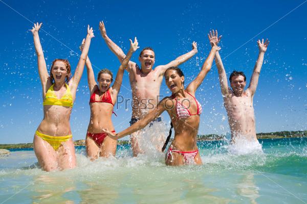 Счастливые подростки веселятся в озере разбрызгивая воду и подняв руки вверх